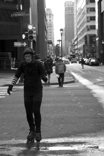 An elderly woman whizzes across John F Kennedy Boulevard, Philadelphia, showing off skills that surpass those of my own!