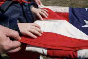 A grandfather teaches his grandson how to fold an American flag.