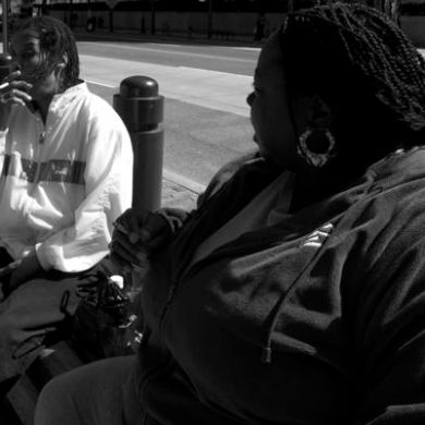 Two sisters on Market Street, Philadelphia take a break from the hustle and bustle to continue a 20 and 30 year tradition of smoking.