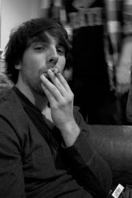 A young man sits out a at party for a moment to enjoy his cigarette.