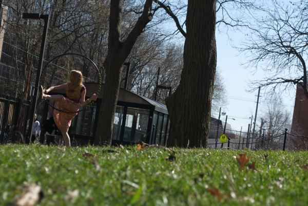 A hula hooper swings some tricks outside the Paley Library, Temple University.