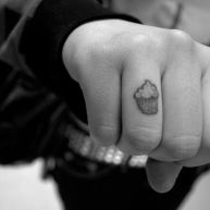 A cupcake tattoo on the ring finger of an art student.