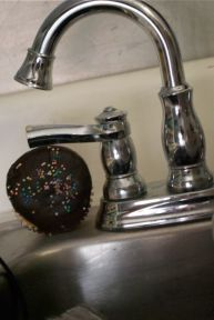 A stray cupcake has escaped and taken shelter under a faucet knob.