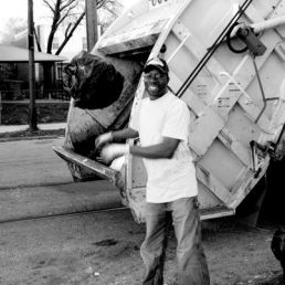 A sanitation worker does his job by gathering up the garbage from the city.