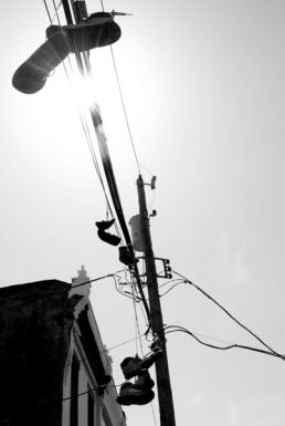 Shoes hang from the electrical wires day in day out, basking in the afternoon sun.