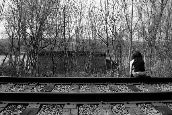 Holly Cieczko sits pensive on train tracks along the Susquehana River.