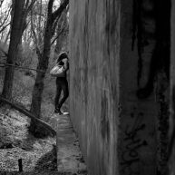 Holly Cieczko peeps around the corner of an old building along the Susquehanna River