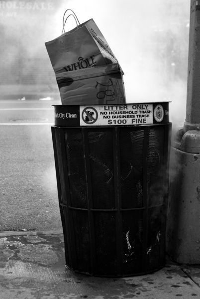 I notice a smoking garbage can on a corner in New York City, taking a better look, I see there is a small fire at the bottom.