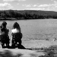 Betty Breznay and Holly Cieczko sit in plastic wrought iron chairs watching the Susquehanna River go by.