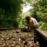 Holly Cieczko rummages through her purse on train tracks, slowly conquering a long time fear of trains.