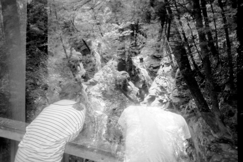 A double exposure of Brittany Bradford and Thom Shubilla gazing over one of the bridges at the Seven Tubs Nature Area into one of the tubs.