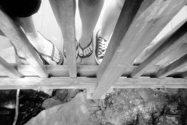 From left, Thom, Betty, Brittany, and Holly's feet on the bridge through the spokes at the Seven Tubs.