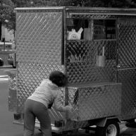 In Harm's Way: A woman slowly pushes her food cart out of the way of traffic.