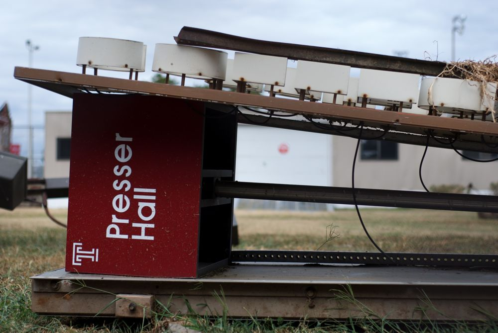 An old sign for Presser Hall lies on its side, defeated, in a junkyard on Temple's campus.