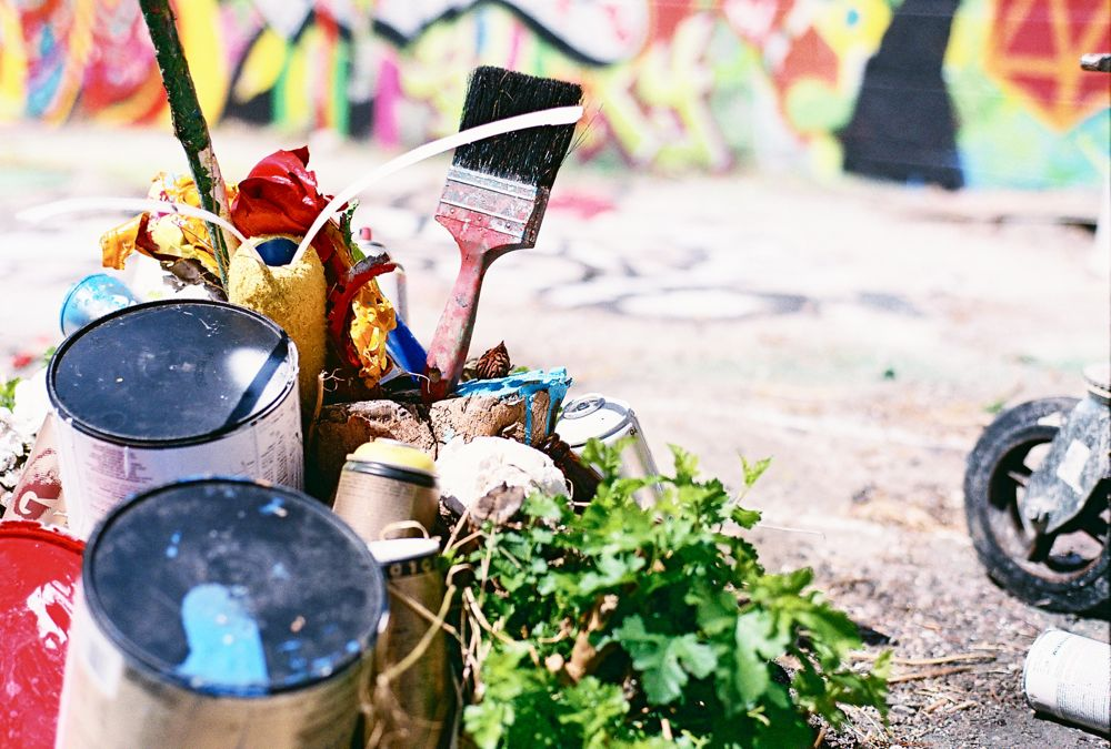 A pile of paint cans and used brushes at the site of the Cosmic Terrarium mural painting during the Philly Fringe Festival.