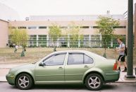 A green car, in front of a green lawn, with green trees, in front of the Tyler School of Art with green walls inside. And some guy.