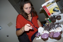 Julia Hewitt attempts to tie-dye a cupcake with food coloring.