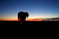 Holly takes photos of herself against the sunset. The red auto-focus assist light illuminates her, matching her face to the sky.