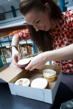 Inga attempts to take the first cupcake out of the box - always a challenge.