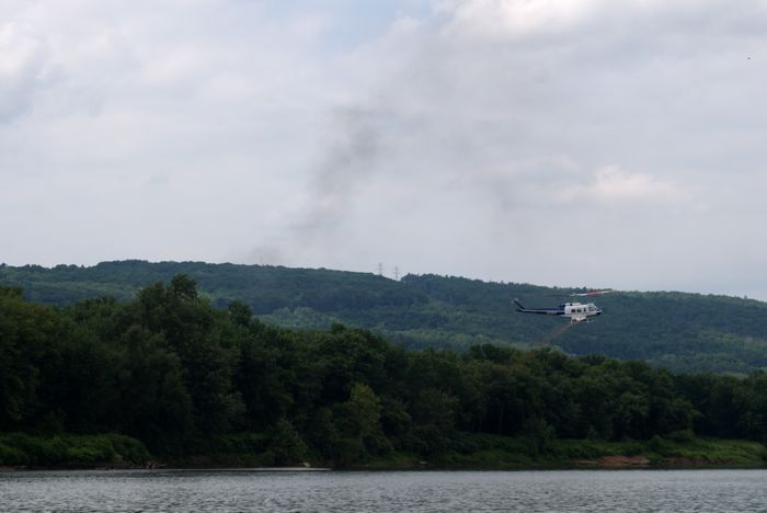 The helicopter sprays orange substance on the other side of the river.