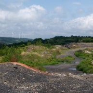 Tourists dot the steaming landscape of Centralia while windmills blow away ancient coal energy.