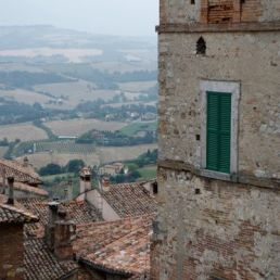 Multiple layers of building facades, roofs, and countryside comprise this beautiful landscape.