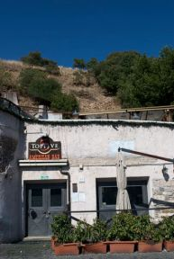 """A man made hill of clay pot shards in Testaccio (translated """"fired clay"""") behind an American bar apparently."""