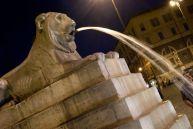 A lion fountain around the obelisk of Piazza del Popolo.