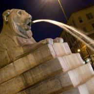 A lion fountain around the obelisk of Piazza del Popolo.