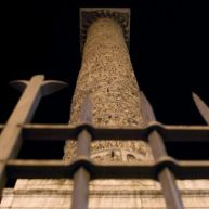Marcus Aurelius's column, behind bars, at night.