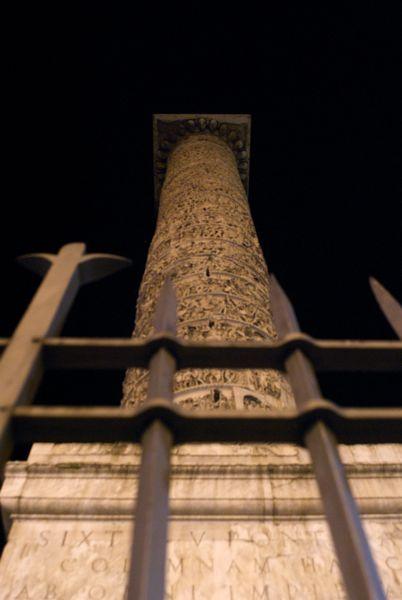 Marcus Aurelius's column, behind bars, at night.