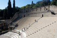 Tourists march up the cavea of the large theater at Pompeii.